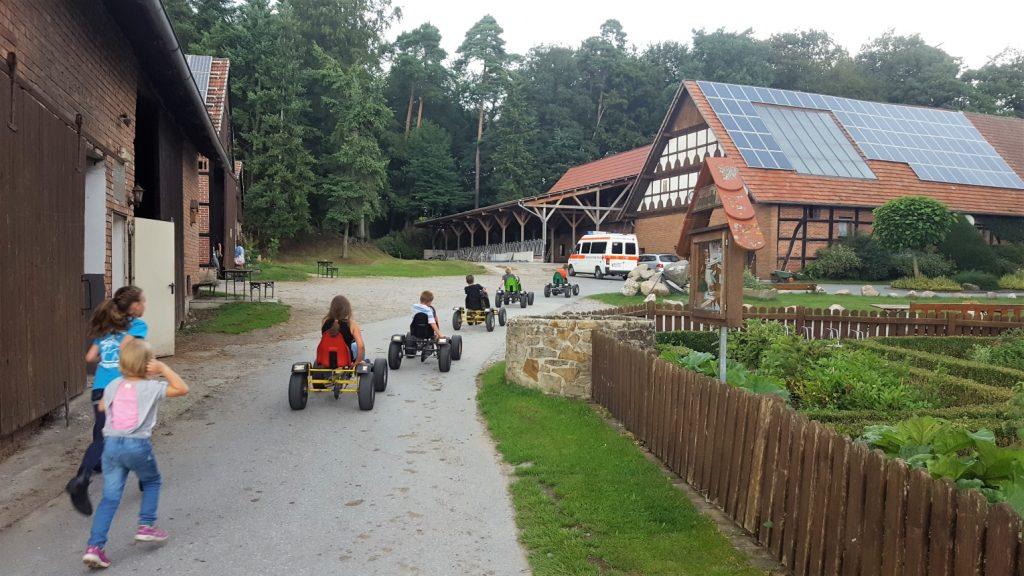 Auf dem Seglinghof toben. Kinder beim Kart fahren